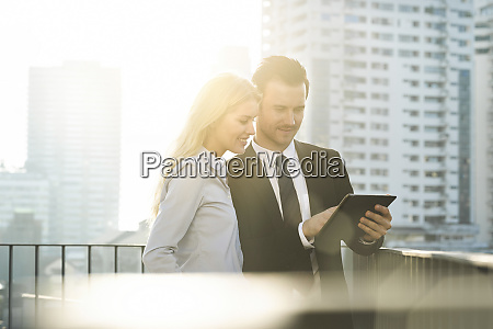blonde businesswoman and male colleague using