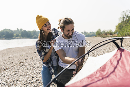 happy young couple setting up a