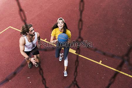 young man and woman playing basketball