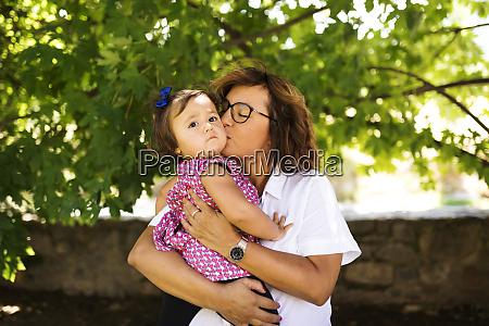 mature woman kissing serious baby girl