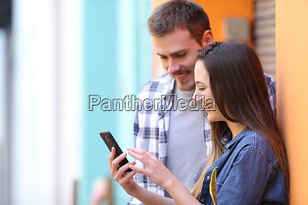 happy couple browsing smart phone content