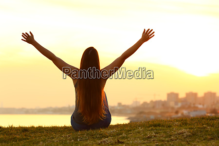cheerful woman raising arms at sunset