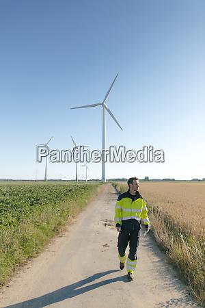 engineer walking on field path at