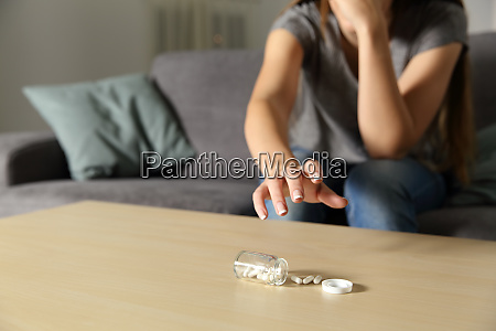 depressed girl catching antidepressant pills