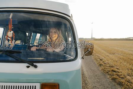 happy young woman driving camper van