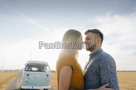 affectionate young couple at camper van