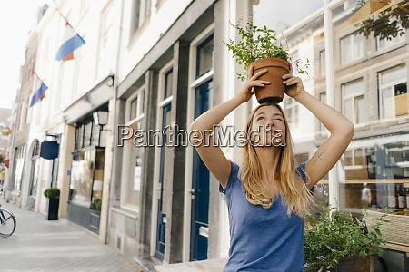netherlands maastricht young woman balancing flowerpot