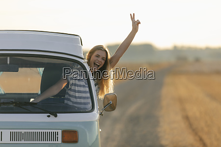 excited young woman making victory hand