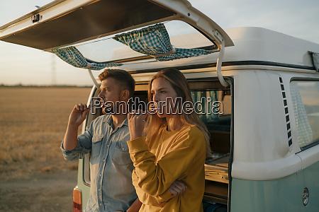 couple brushing teeth at camper van