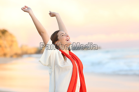 excited woman celebrating sunset raising arms
