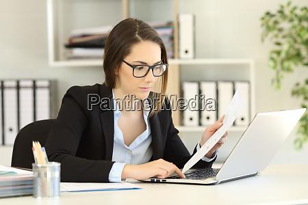 executive entering data in a laptop