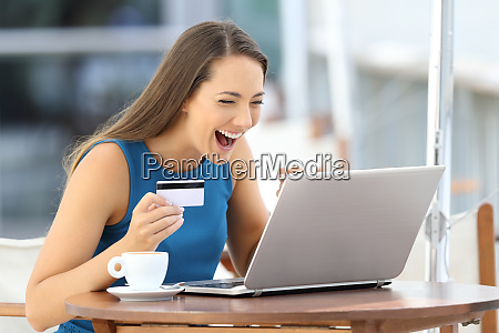 excited woman paying on line with