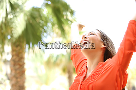 excited woman raising arms outdoors