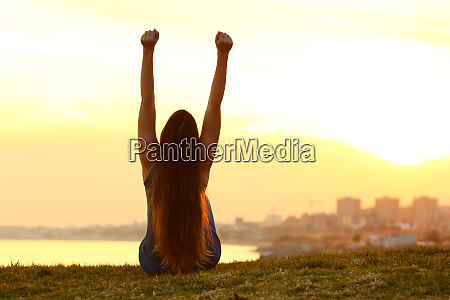 excited woman raising arms watching the