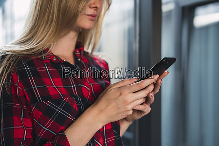 hands of young woman holding smartphone