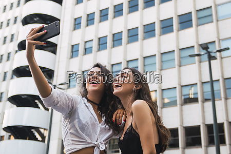 laughing friends taking selfie with cell