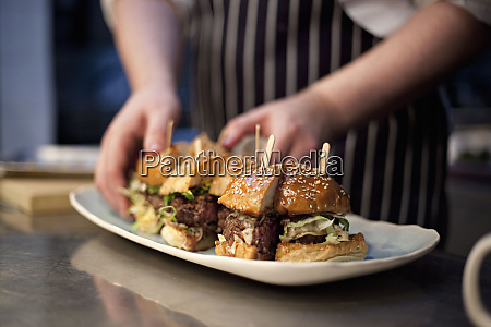 a chef plating up burgers