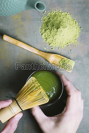 preparing matcha tea with bamboo whisk