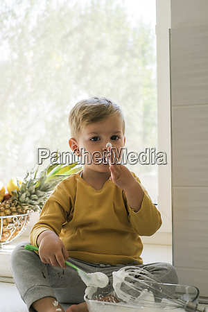 portrait of little boy nibbling whipped