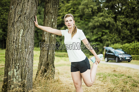 sportive young woman stretching at a