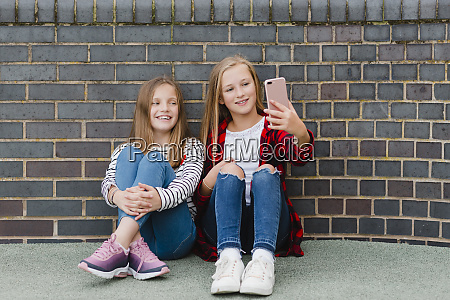 portrait of two smiling girls sitting
