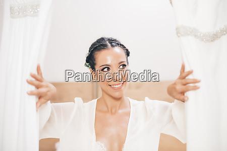 smiling woman opening curtain looking sideways