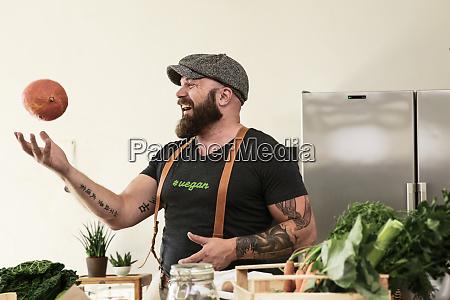 vegan man playing with a pumpkin