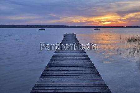 wooden jetty at sunset at lake