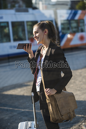 smiling young woman with luggage at
