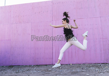 exuberant young woman jumping in front