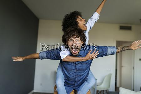 cheerful man carrying girlfriend piggyback at