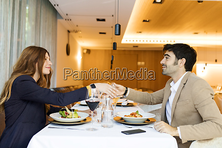 smiling man and woman shaking hands