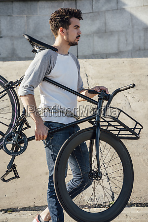 young man carrying commuter fixie bike