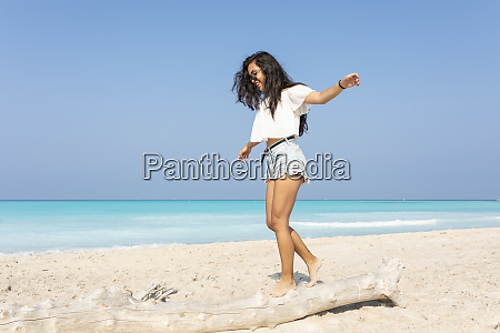 young woman on the beach balancing
