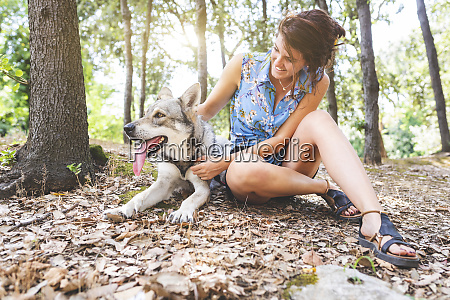 smiling young woman sitting on forest