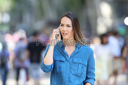serious woman talks on phone on