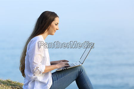 relaxed woman writing in a laptop