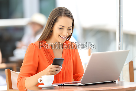 lady using a phone and laptop