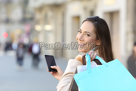 happy shopper holding phone and shopping