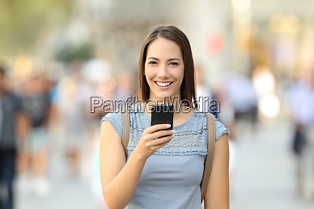 happy woman holding a phone looking