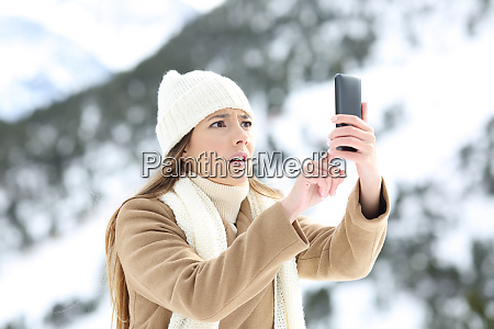 woman searching phone coverage in winter
