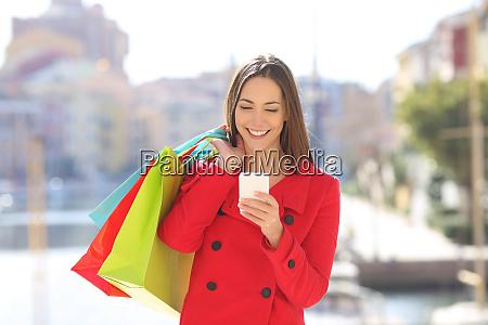 happy shopper tourist using a phone