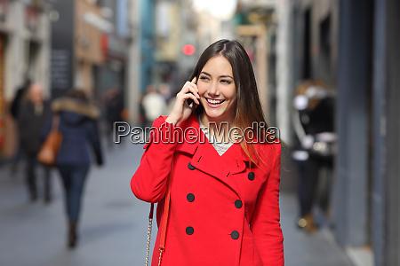 woman in red walking talking on