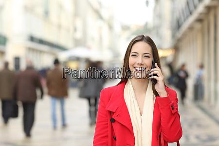 happy female walking talking on phone