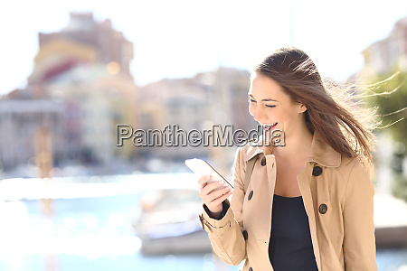 happy woman laughing watching phone