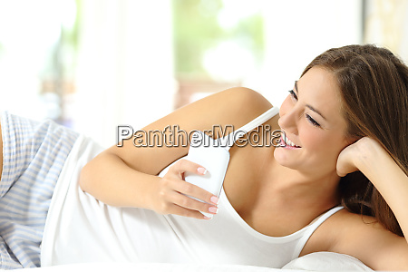 happy woman on the bed checking