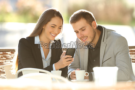 two executives using a smart phone