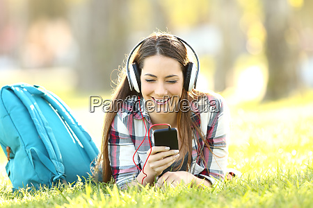 happy student listening audio lessons on