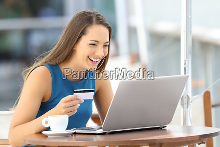 happy woman paying on line with