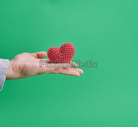 a small knitted red heart in